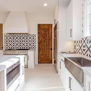 Black and White Mediterranean Kitchen with Carved Wood Door