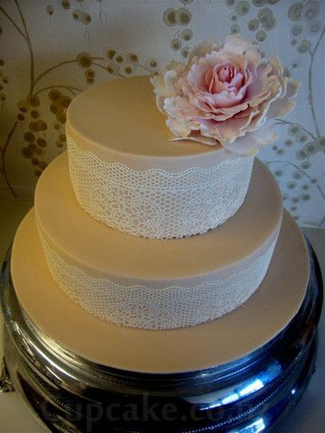 White wedding cake with lace and pink flower