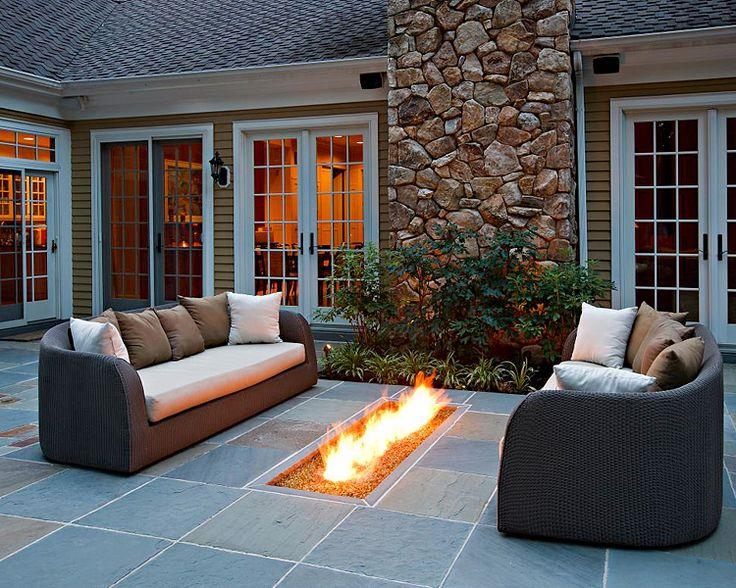 Низко расположенный камин подогревает эту зону отдыха в патио в вечернее время.