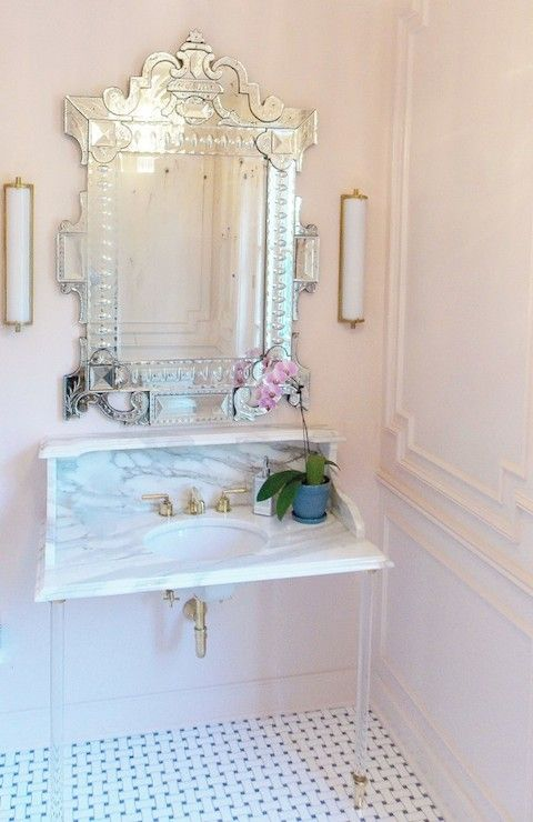 bathroom features pink walls accented with pink wall moldings alongside Venetian mirror illuminated Calliope Bath Lights in Hand Rubbed Antique Brass over lucite washstand topped with white marble framing round sink as well as marble backsplash with shelf atop mosaic marble floor.