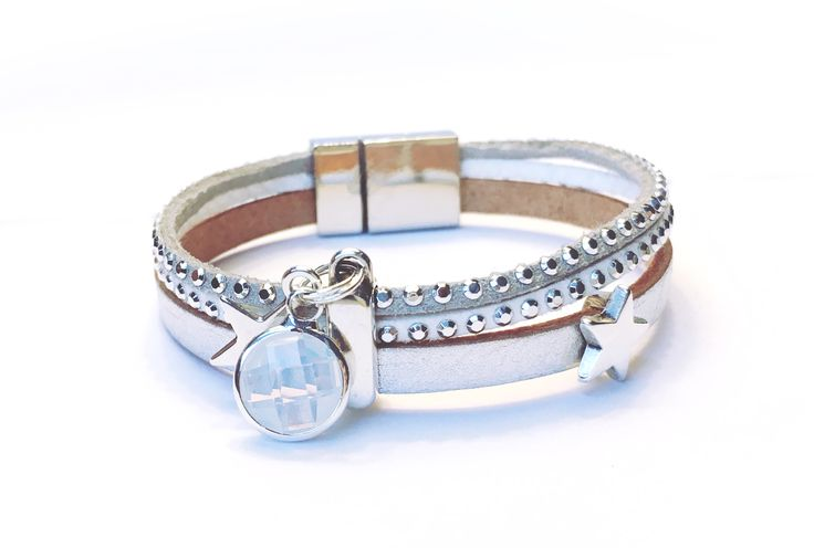 Unieke handgemaakte armband in de kleuren wit en zilver en licht-grijs. Met een mooie schuivers voorzien van swarovski steentjes en zilveren bedels. De amband heeft een zilveren magneetsluiting.