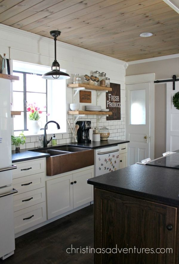 Красивый фартук передний чеканная медная раковина является координационным центром этой кухне. Люблю плитки метро, открытые стеллажи, белые шкафы и черный гранит столешницы. по MyohoDane