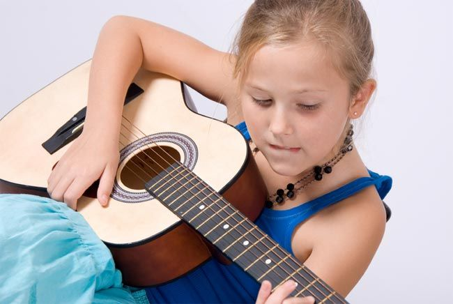 Strumming that guitar could help this little girl not only with dexterity, but also with brainy vocabulary tests.