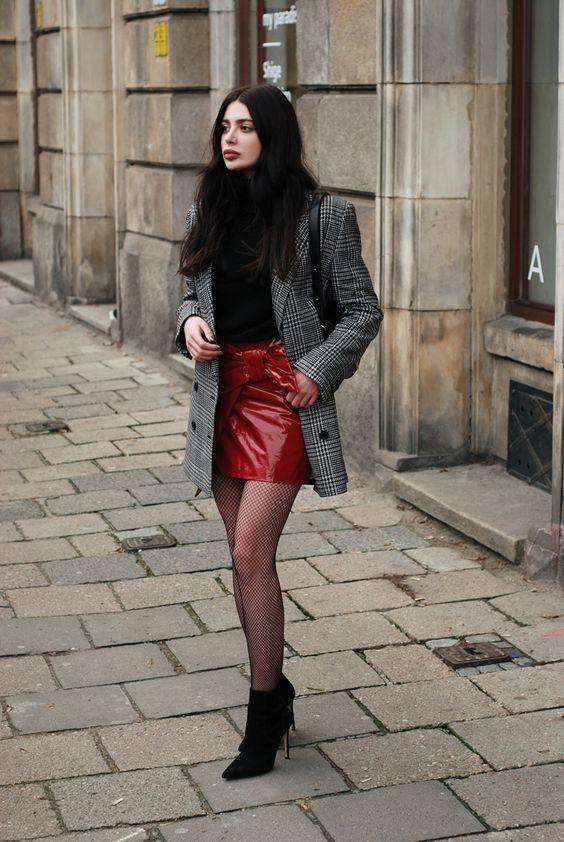Dupla estilosa: minissaia + maxi blazer. Blazer cinza xadrez, blusa de gola alta preta, saia vermelha de vinil, meia arrastão preta, ankle boot preta com bico e salto fino
