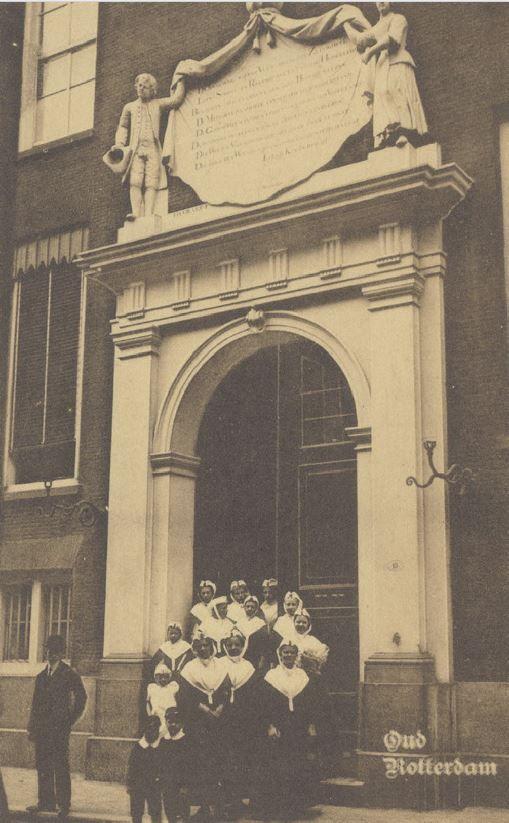 Weesmeisjes en jongens voor de hoofdingang van het Gereformeerd Burgerweeshuis aan de Goudsewagenstraat. Boven de ingang is een gevelsteen gebeeldhouwd. Rotterdam. kaart 1920 #ZuidHolland #Rotterdam #wezen #gereformeerd