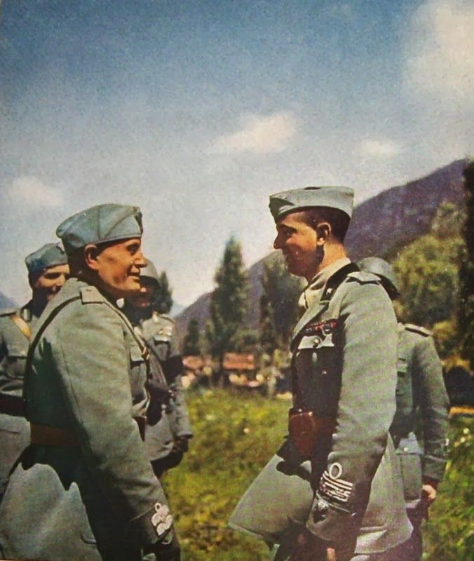 An Italian soldier is greeted by Benito Mussolini. -