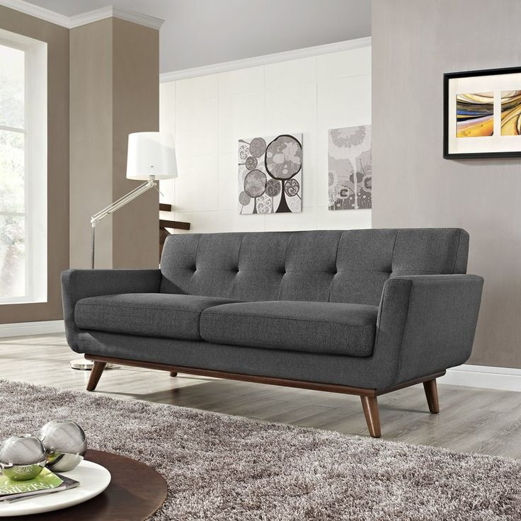 Bring a dash of midcentury modern flair to any seating group with this classic sofa, featuring flared, cherry-finished rubberwood legs and polyester upholstery. Set it down in your living room next to a metal tripod floor lamp and two boxy wood end tables, then top it off with two screen-printed throw pillows and a comfy cashmere blanket for cozy appeal. To round out the rest of your seating group, set down a gray shag rug under a glass-topped coffee table, then arrange a clean-lined…