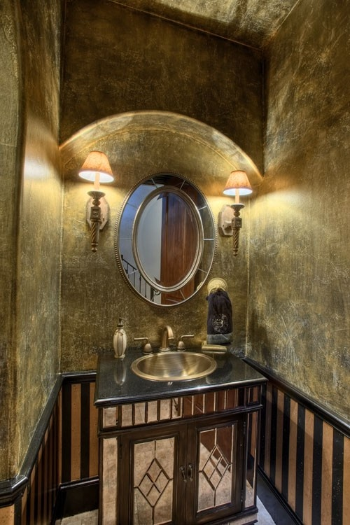 """With """"antiqued"""" metallic gold walls and fixtures and black striped trim, this powder room has an ancient Egyptian feel."""