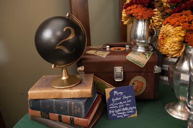 A travel themed wedding table with books globe