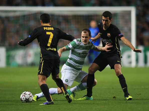 Anthony Stokes of Celtic is foiled by Pedro (L) and Sergio Busquets of Barcelona (R) during the UEFA Champions League Group H match between Celtic and FC Barcelona at Celtic Park Stadium on October 1, 2013 in Glasgow, Scotland.