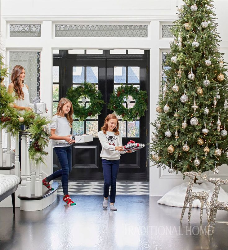 The foyer, decked in black-and-white tile and leaded-glass windows, establishes the holiday season with a soaring tree, greenery woven through the stair railing, and a pair of wreaths, all from Frontgate. - Photo: Werner Straube / Design: Soledad Zitzewitz