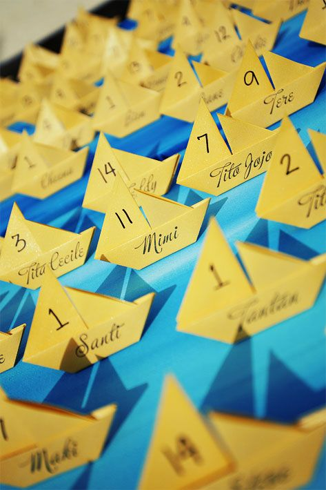 Escort cards: Origami sailboats personally folded by the bride were placed on monochromatic blue-painted canvas.
