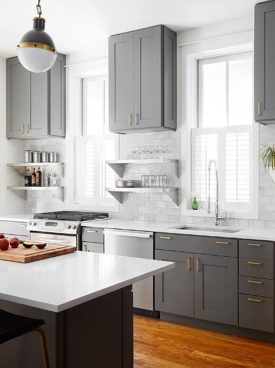 Stunning Charcoal Gray Kitchen Boasts A Gray Center Island Topped With A White Quartz Countertop Facing
