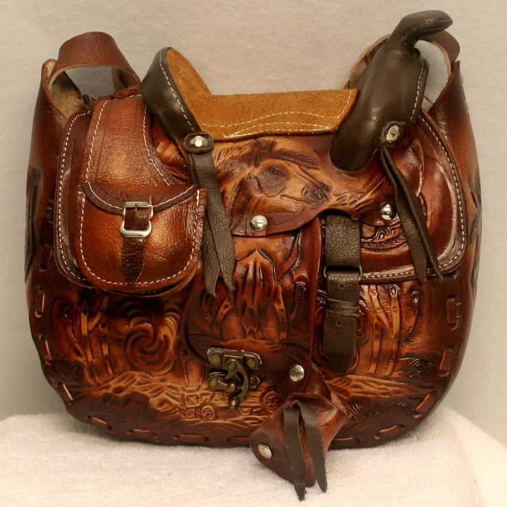 Leather Hand Tooled Saddle Purse is complete with stirrups, saddle bag, belly band, and wool lining under the saddle. A real show stopper and conversation starter!