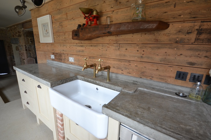 Polished concrete, shaker cabinets and reclaimed floor boards for wall panelling.  An eclectic kitchen designed and installed in Guernsey