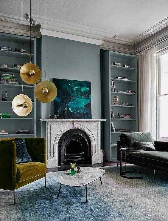 Although I'm not entirely sure about that cymbal(?) lighting fixture, love everything else about this living room: dusty turquoise, white, olive and pops of gold/brass, marble fireplace surround, built-in bookcases painted the same grayed turquoise as the walls, velvet upholstery. Moody abstract painting propped on the mantel. So good!