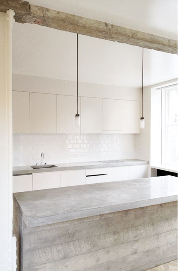 Subtle hanging lights and sleek materials and textures complete this modern kitchen.