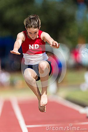 Young girl athlete in mid flight of her long jump effort and a province or state event. Telephoto picture image sequence of the ten year old female in a red top and dark blue shorts focusing on her leap effort through the air.