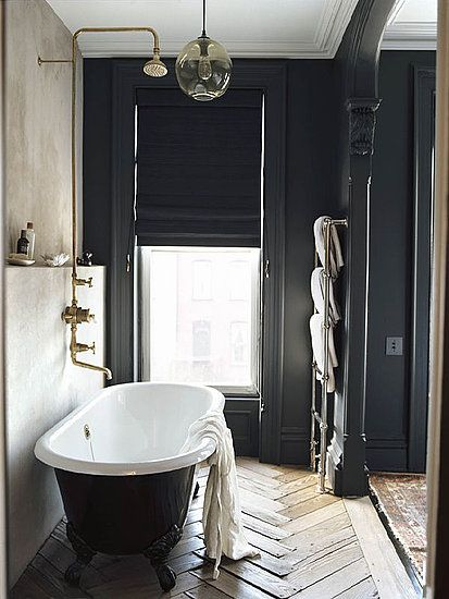 J.Crew Creative Director Jenna Lyons Sells Park Slope Townhouse For $4 Million: The master bedroom's moody dark walls create a chic look. : An en suite bathroom features a clawfoot tub. : Herringbone floors add personality in the bathroom.