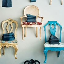 Chair display - chairs on the wall or fence with potted plants on them - love it