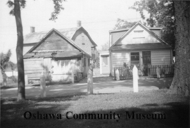 Black and white photograph of cottages in Lakeview Park with Robinson House in the background.
