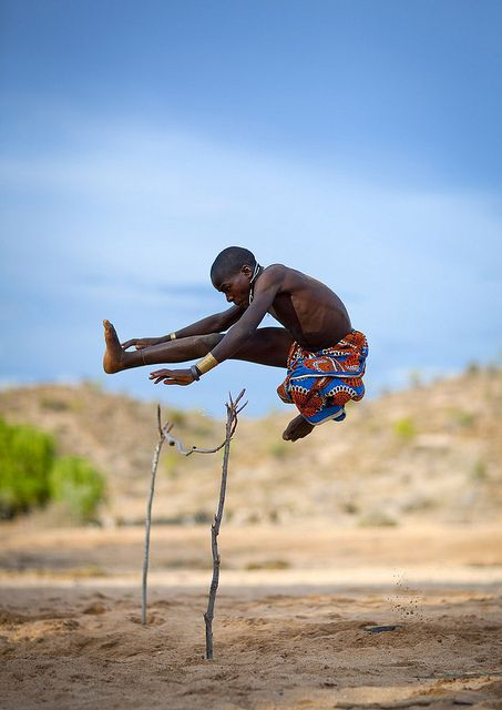 Mukubal Kid Doing High Jumping, Angola    Mucubal people are a subgroup of the Herero ethnic group, which means they are bantu speaking, and are supposed to have come from Kenya and to be related with Massais. They are semi nomadic pastoralists living of cattle raising and agriculture. They live in a large area between the slopes of Chela Mounts in the north, and River Cunene to the south, where they are believed to have stopped during the Herero migration, about 300 years ago.   Mucubal…