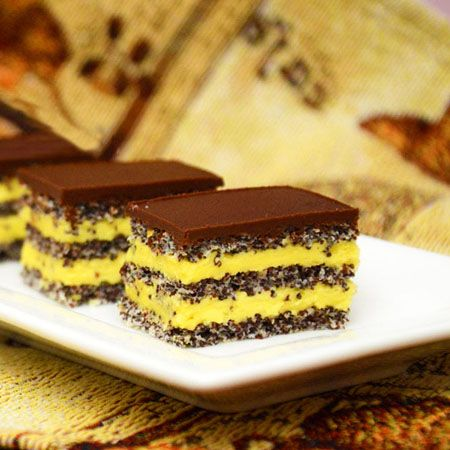 Prajitura cu blat de mac si crema de vanilie este un desert savuros ce se prepara foarte usor. Blatul de mac combinat cu crema de vanilie si topping-ul de ciocolata, alcatuiesc o prajitura excelenta. Ingrediente Prajitura cu blat de mac si crema de vanilie: Blat: 9 albusuri 200 grame zahar