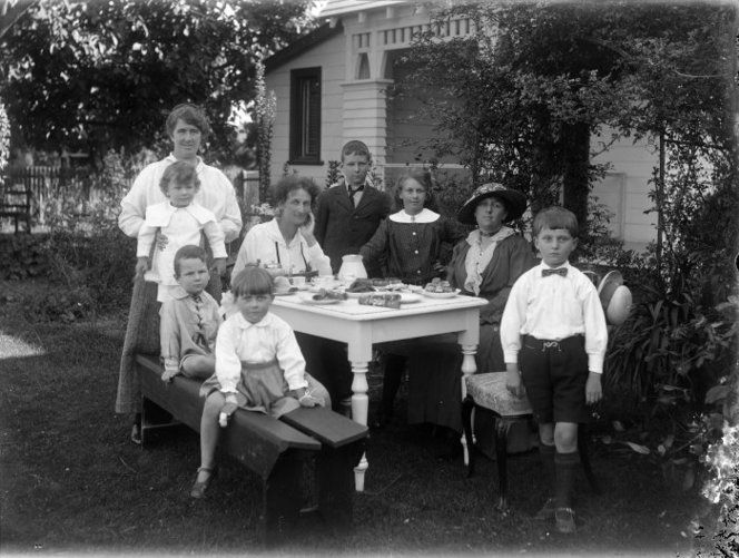 Group of women and children, in a garden, around a table laid out with afternoon tea items 1910c