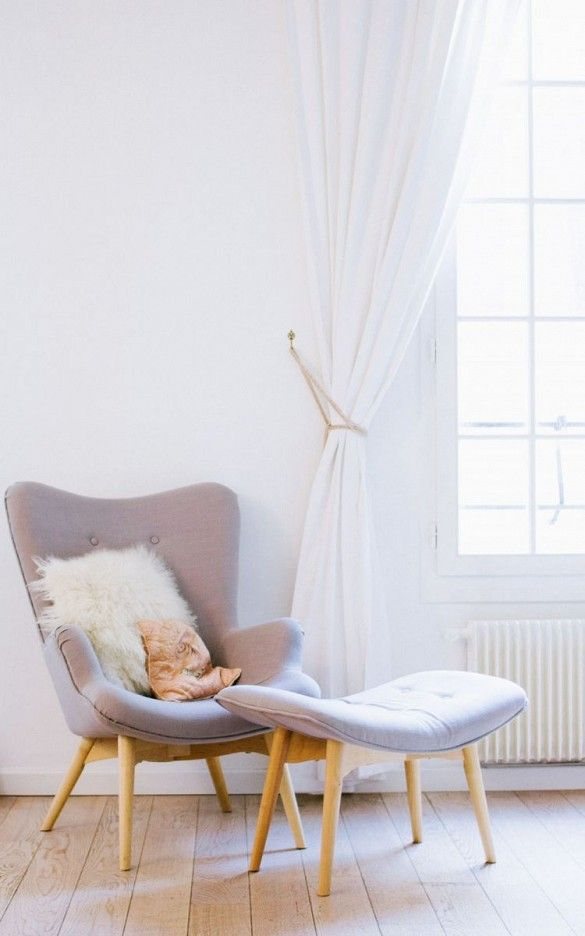 Matching grey fabric armchair and foot stool with fur pillow by a large window with all white curtains.