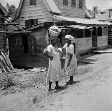 Vrouwen in een woonwijk in Suriname (1947). Fotocollectie Van de Poll.