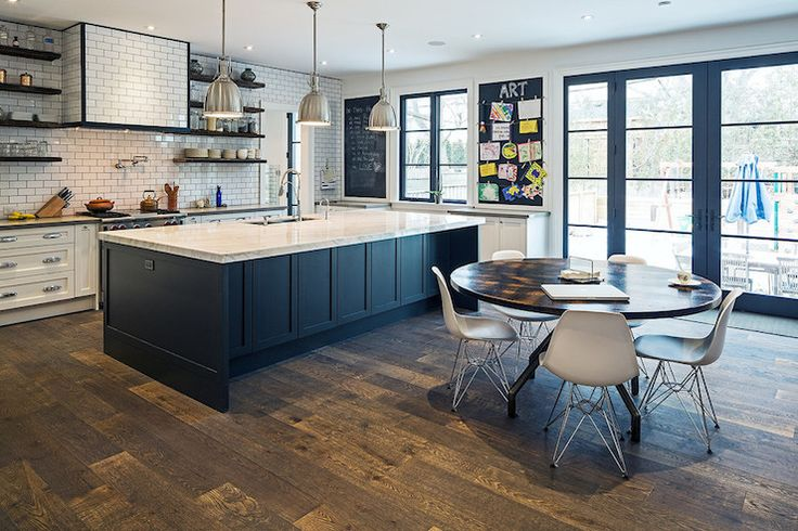 Eat-in kitchen featuring white perimeter cabinets, black island, chrome pendants, floating shelving, subway tile, chalkboard and art station