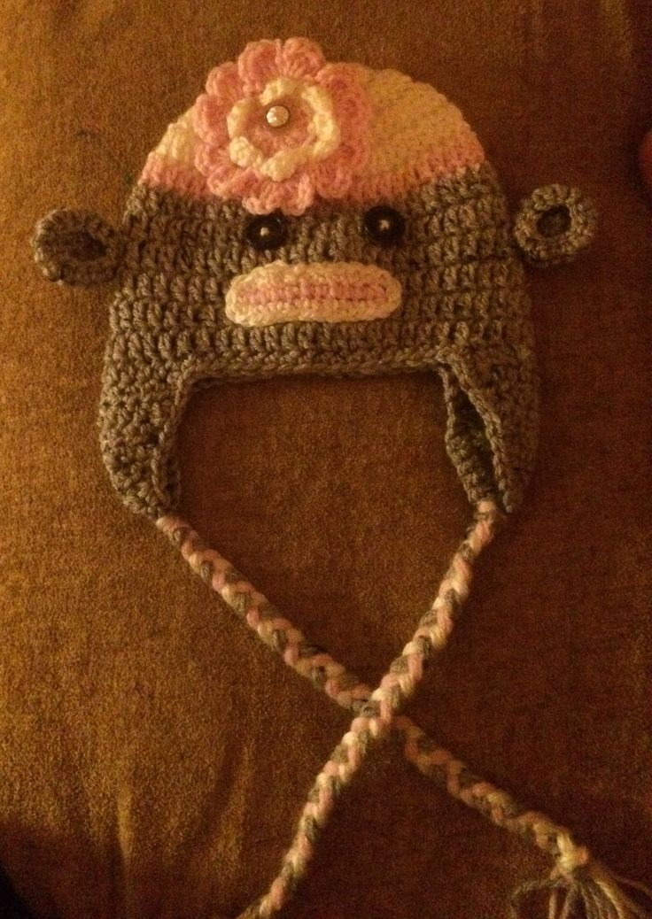 Girls sock monkey hat I made with braids and a flower. It's crocheted.