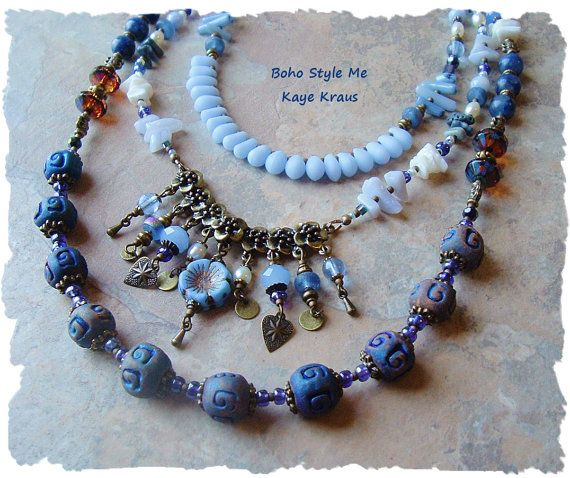 This multi-strand blue art necklace ranges from a light periwinkle blue to deep cobalt blue. Three unique strands join together at beautifully faceted, brass wrapped clear crystals. Rich in gemstones, rustic earthy clay beads, freshwater pearls, coral, shell, and crystals, this necklace is clearly a one of a kind statement piece. Picasso finished glass, quality Czech glass and three glass flowers, from England, are positioned throughout. Below a strand of blue frosted teardrops, is a floral…