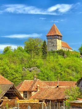 Villaggio della Transilvania del Rodbav con la chiesa sulla collina, la Romania. photo
