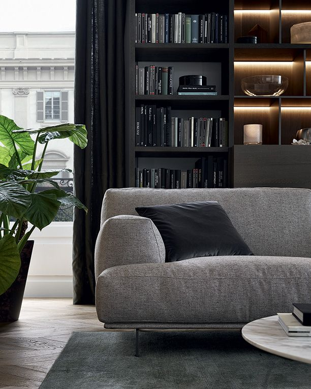 Tribeca sofa and pouf with 11 sabbia Oxford removable fabric covering, cushions in 1404 carbone Persia velvet. Baba coffee table with piombo painted metal frame and mat emperador dark marble top. Tribeca coffee table in piombo painted metal and top in mat calacatta oro marble.