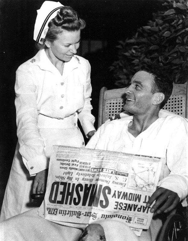 Ensign George H. Gay at Pearl Harbor Naval Hospital with a nurse and a copy of the Honolulu Star-Bulletin newspaper featuring accounts of the battle. He was the only survivor of the June 4, 1942 Torpedo Squadron Eight (VT-8) TBD torpedo plane attack on the Japanese carrier force. Gay's book Sole Survivor indicates that the date of this photograph is probably June 7, 1942, following an operation to repair his injured left hand and a meeting with Adm. Chester W. Nimitz. National Archives photo