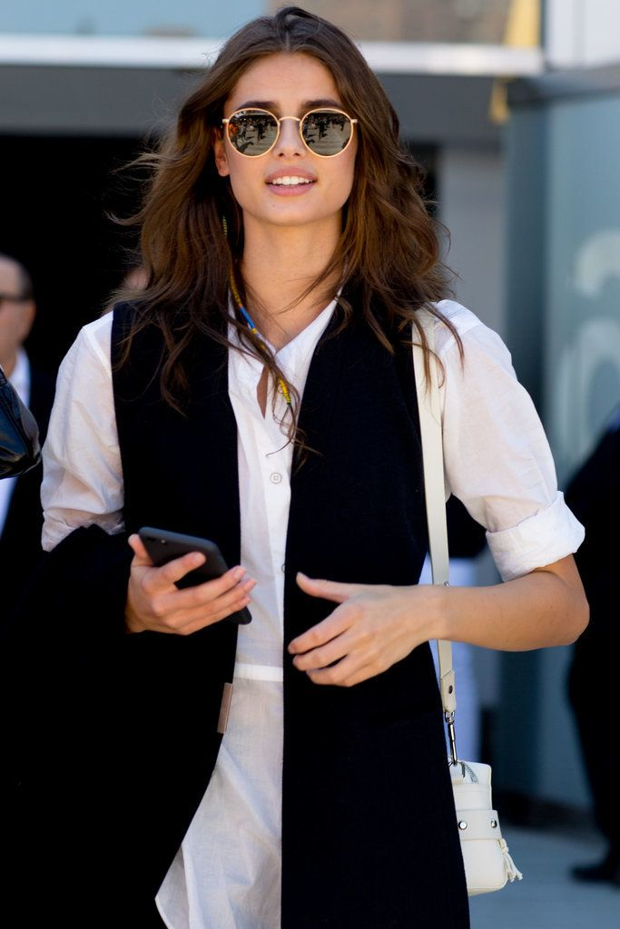 A long black vest, a white button-down, and round sunglasses