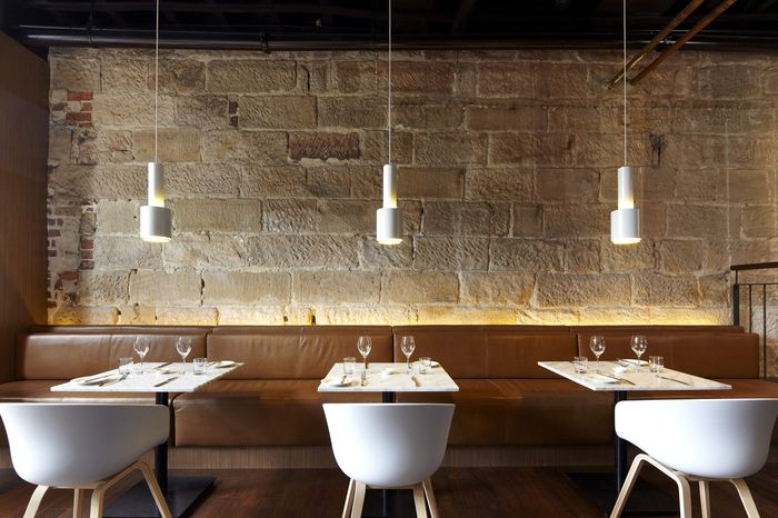 Scarlett - SJB Interiors Black ceiling, stone wall, back lighting, simple clean elegance.
