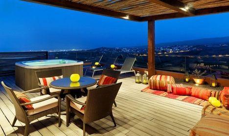 Оригинально оформлена терраса на крыше дома. Она большая и просторна. Визуально терраса разделяется на две зоны. В одной из зон поставили круглый стол и кресла с мягкими подушками, также постелили ...