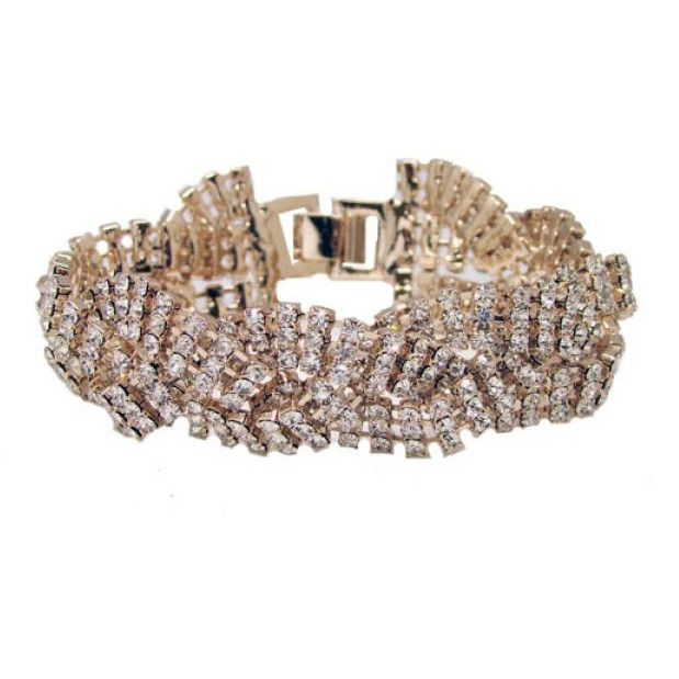 The gold Drew Bridal Bracelet is designed with a wave plated pattern with clear rhinestones. This piece is 14k gold plated.Approximately 18.5CM LONG