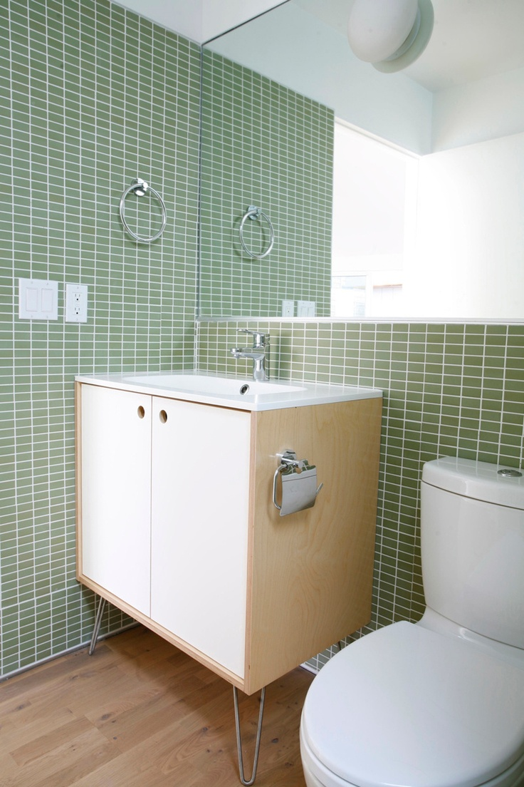 In the bathrooms, Sweet used a mirror to enlarge the feel of the space. They kept the costs minimal by using Grohe bath fixtures and an Ikea sink.