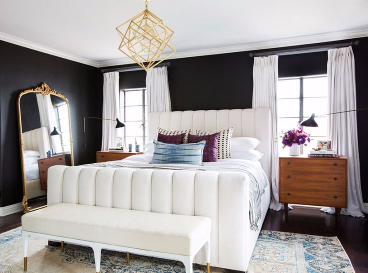 Sublime bedroom where an extraordinary bedroom meets with two repurposed chests of drawers work as nightstands. The luxury touch is provided by the wall mirror and a stunning golden chandelier.