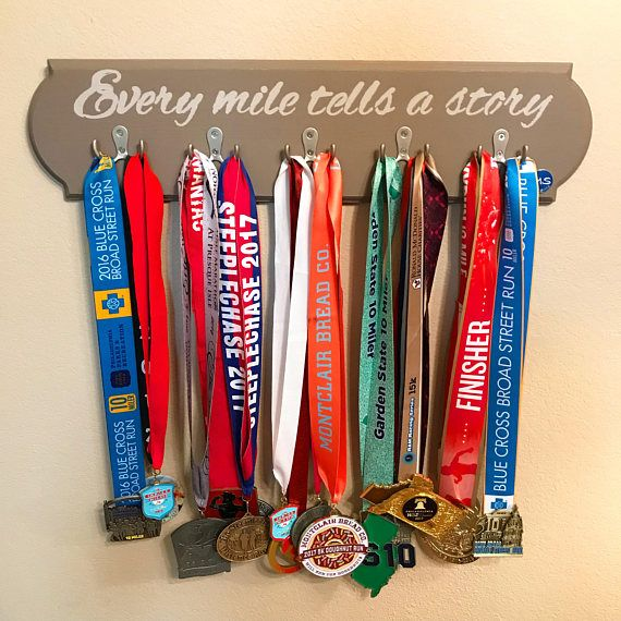 The Road Less Traveled Medal Swing  Our product is a hand crafted, made-to-order wooden hanging medal display holder with a decorative routered edge. This Medal Swing is painted a neutral gray with a light gray paint for the lettering. The words Every mile tells a story is painted across