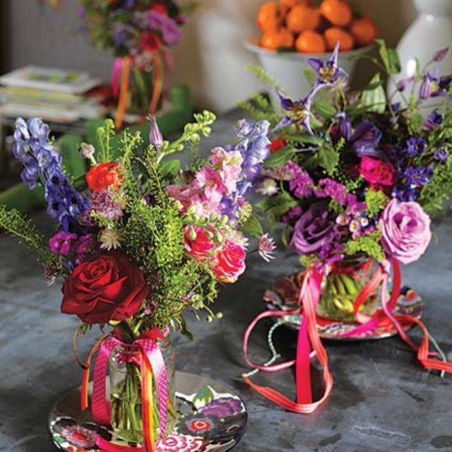 Table flowers: Wild flowers in jam jars which have been decorated with brightly coloured ribbons.