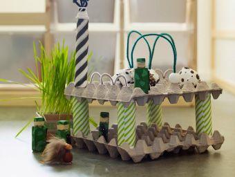 Gros plan d'une construction faite avec des cartons d'œufs et du carton et décorée avec du papier d'emballage IKEA.