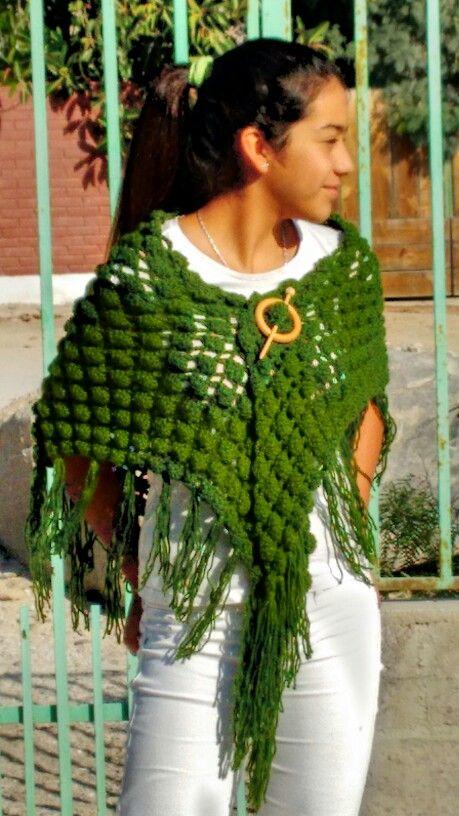 Shawl verde a crohet con accesorio de madera.