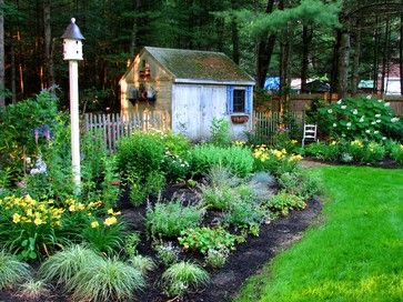 Garden Ornament  A bird house is the focal point of these back yard gardens. The post height ensures plenty of room for tall perennials. The shed has attained a lovely patina including moss growth on the roof. Vintage watering cans on the side of the shed complete the garden theme.
