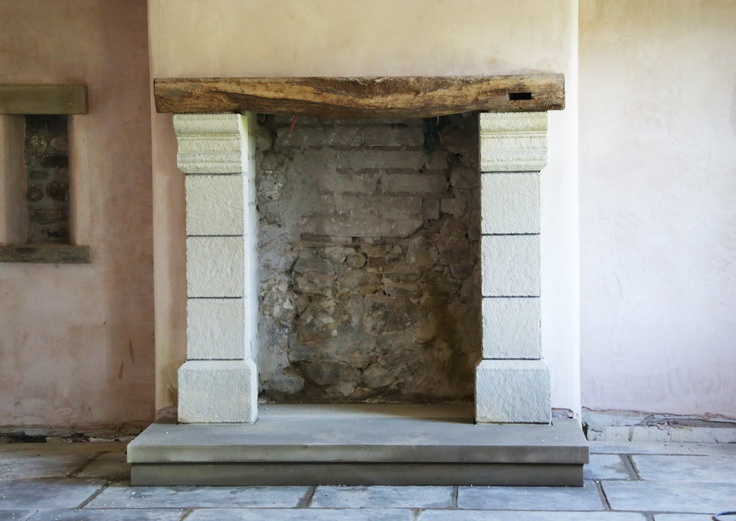 progress on the fire place in front room  The oak beam used on the top was from an outbuilding on the farm and I got the builder to shape blocks of sandstone from my design to make up the sides. Two big Sandstone slabs have been used for the hearth.