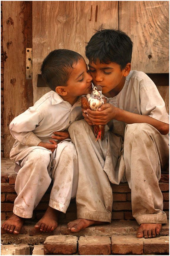 Kids Kissing a Pigeon in Pakistan / Photography by Umair Ghani