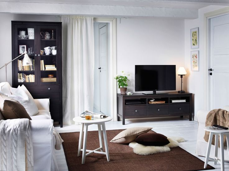 A living room with a white three-seat sofa and nest of tables combined with a black-brown TV bench and a glass-door cabinet with drawers.
